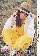 Woman dressed in yellow dress, white jersey and hat sitting...