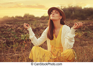Female meditate sitting on a deadwood autumn field. - Young...