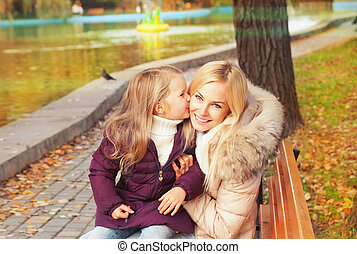 Happy mother with daughter have a rest sitting in autumn park on a bench.