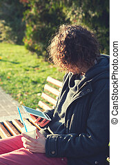 Man sitting in autumn park on a bench, reading the...