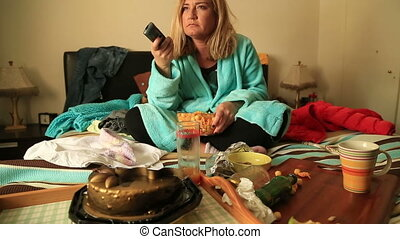 Depressive woman eating chips and watching tv