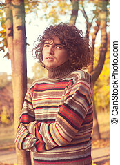 Attractive young man with long curly hair, dressed in...