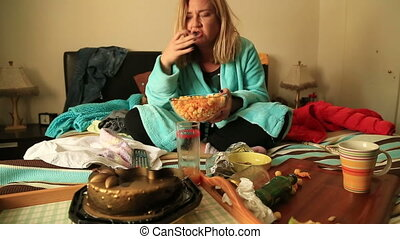 woman eating chips and watching tv - Depressive woman eating...