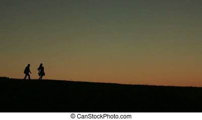 Silhouette of  Beautiful Couple Playing Catch  Against  Sunset On The Backgrund Close Up