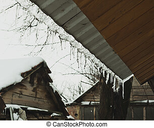 Icicles hanging on the roof of the house