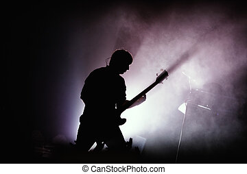 guitarist at rock concert - Black silhouette of guitarist at...