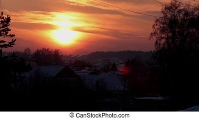 sunset in the winter willage with smoke coming from chimney pipes