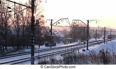 Electric train moving from right to left at winter sunset