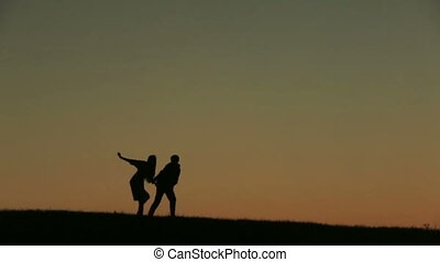 Silhouette of  Beautiful Walking Against  Sunset On The Backgrund Close Up