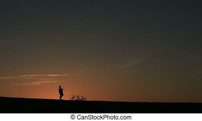 Silhouette of Beautiful Couple With Tandem Bicycle. Man...