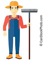 Farmer with rake - An asian farmer standing with a rake...