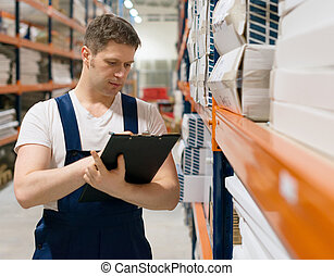 Supervisor with clipboard checking barcode at the warehouse.