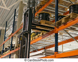 Warehouse storage racks with goods and forkslift.