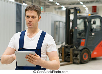 Handsome supervisor with tablet pc at the warehouse.