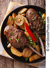 Beef steak with chili and fried potatoes close-up vertical...