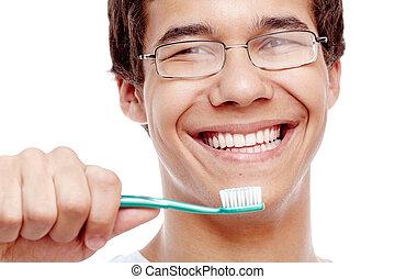 Toothy smile with brush closeup - Face close up of young...