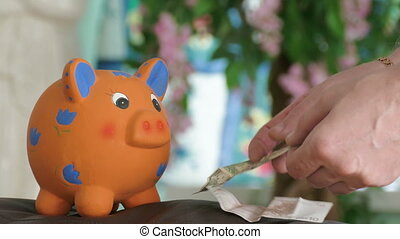 piggy bank waiting for money - young man putting money in...