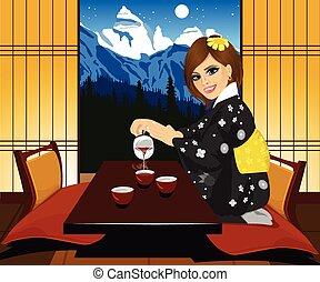 Attractive woman in kimono pouring tea Interior of...