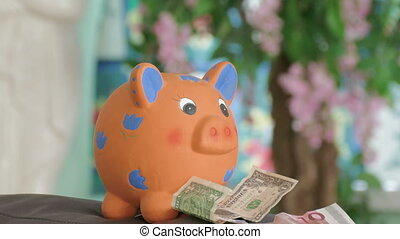 piggy bank - young man putting money in piggy bank
