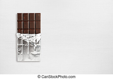 Chocolate bar in foil on wooden table top view