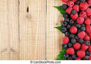 Raspberries on wooden background top view
