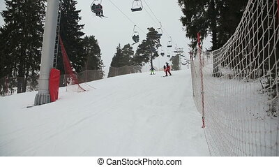 Skiers and snowboarders skiing downhill - Skiers and...