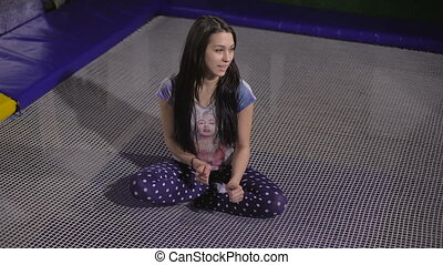 Jumping on trampoline Young woman fun - A young woman in a...