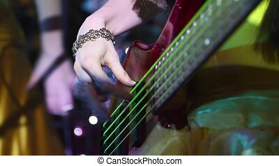 girl playing electric guitar in a club