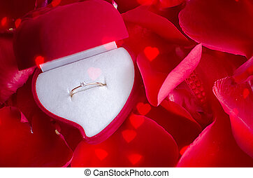 Engagement ring and red rose petals - Red velvet box with...