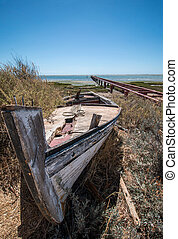 Abandoned boat on the vegetation on the sand dunes of Ria...