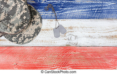 USA national colors with military cap and ID tags on wooden...