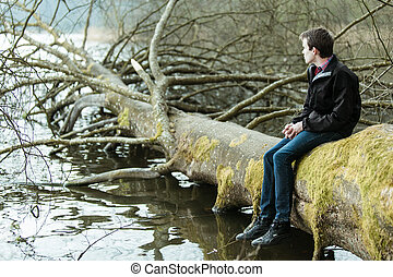 Teenage boy sitting on a fallen tree trunk