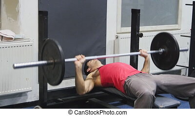 Men lifts up a barbell as a chest exercise.