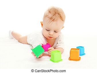 Baby lying playing with colorful toys on white background