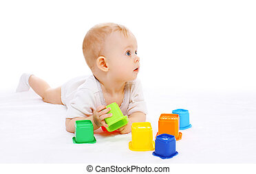 Cute baby lying playing with toys on white background