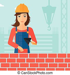 Bricklayer with spatula and brick - A female bricklayer with...
