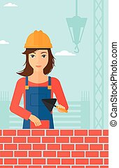 Bricklayer with spatula and brick. - A female bricklayer...