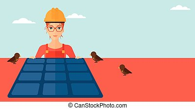 Constructor with solar panel - A woman installing solar...