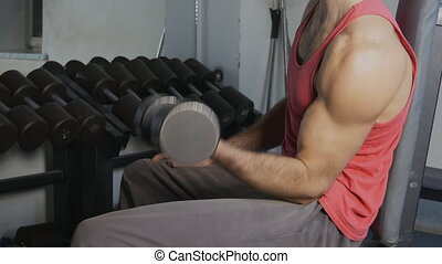 Hands with dumbbells of man in gym hall.