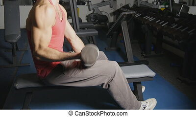 Hands with dumbbells of man  doing exercising in gym.