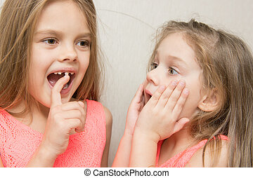 Six-year girl showing her sister loose baby tooth - Six year...