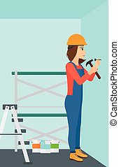 Constructor hammering nail - A woman hitting a nail in the...