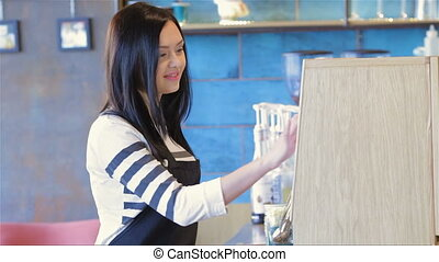Female waiter in a cafe at the checkout. A charming female...