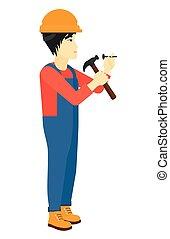 Man hammering nail. - An asian constructor hitting a nail...