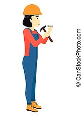 Woman hammering nail - An asian constructor hitting a nail...