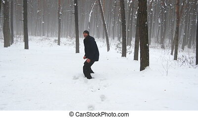 Happy man playing snowballs in the forest