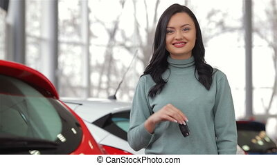 Smiling woman with car key outside Auto business, car sale,...