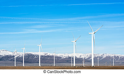 Winter mountains with windmills - Wind turbines on a farm in...