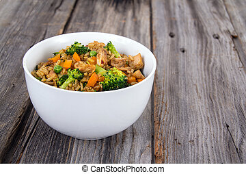 chicken and vegetable rice bowl on a old wooden grey wood...