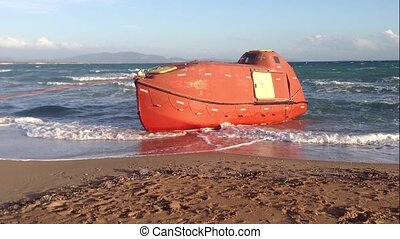 Capsule lifeboat on the seashore after crushing. Modern...